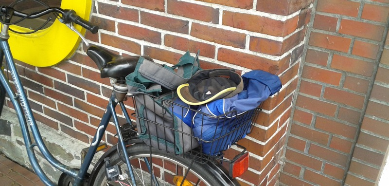 Fahrradkorb hinten auf dem Gepäckträger mit Arbeitskleidung