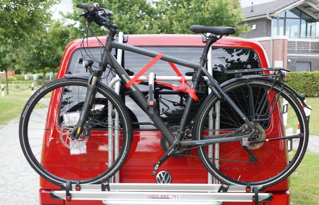 Fahrrad aufgeladen und mit Spanngurt am Fahrradträger gesichert