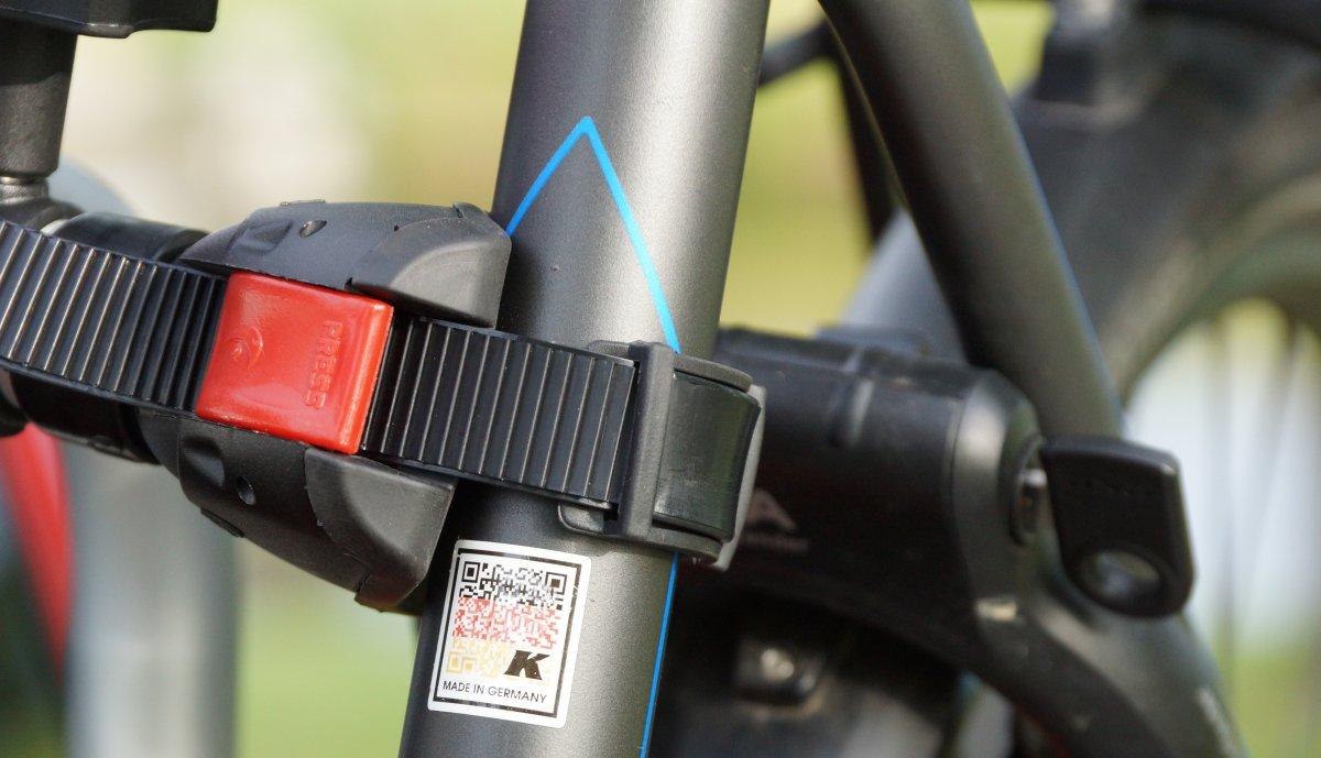 Fahrrad mit Greifarm fixieren auf dem Fahrradträger für die Heckklappe